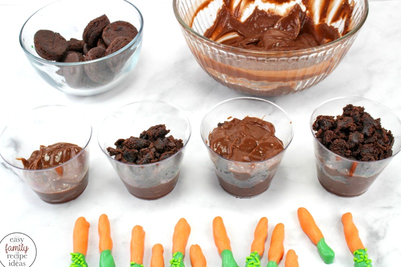 Easter Pudding Cups are so easy to make and the kids love them! These tasty carrot patch pudding snacks are so much fun to eat! Plus, the crunch of the pretzel and smoothness of the chocolate pudding makes them the perfect treat. Dirt Pudding Cups Recipe,carrot patch dirt cups, Easter dirt pudding cups