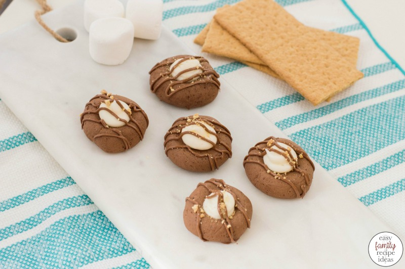 These S'mores Thumprint Cookies are the most delicious cookies and a great winter and fall treat! Great tasting S'mores Cookies are a simple thumbprint cookie kicked up a notch with fluffy marshmallow and chocolate. S'mores Cookies with Graham Crackers make perfect campfire cookies