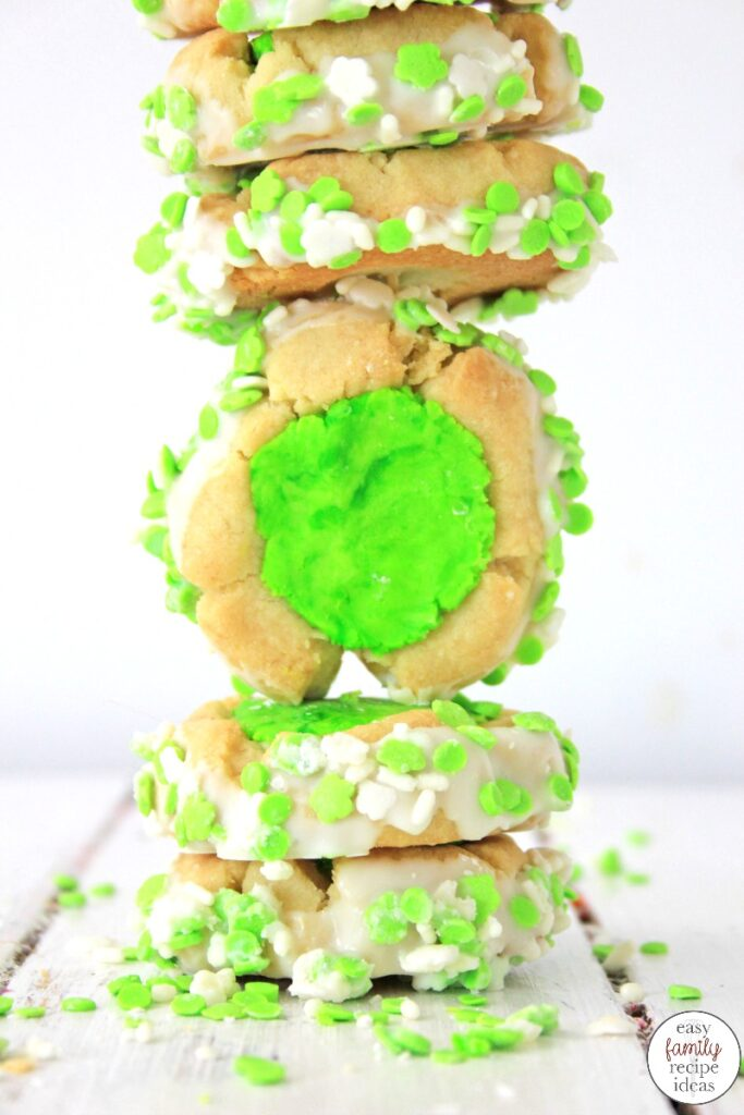 These St. Patrick's Day Thumbprint Cookies dipped in white chocolate and sprinkles, are some of the best you'll ever eat! They're tasty and simple cookies to make and absolutely perfect for St. Patrick's Day! Leprechaun Thumbprint Cookies children and adults love.