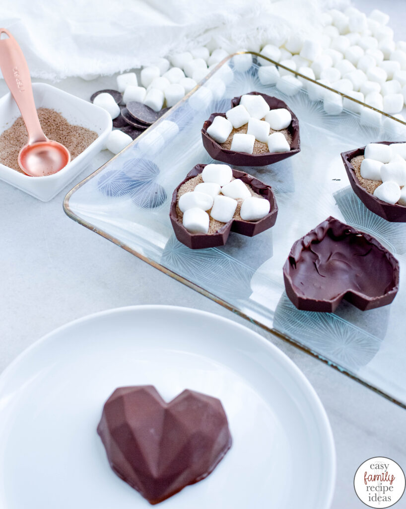 Learn how the make Valentine's Day hot chocolate bombs for enjoying and gifting this Valentine's Day! This hot chocolate bomb recipe is created with heart-shaped chocolate filled with hot cocoa powder and miniature marshmallows. These Heart hot cocoa bombs taste amazing
